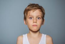 Niño Rubio Con Ojos Azules Y Camiseta De Tiras Blanca Y Cara Seria Mirando De Frente