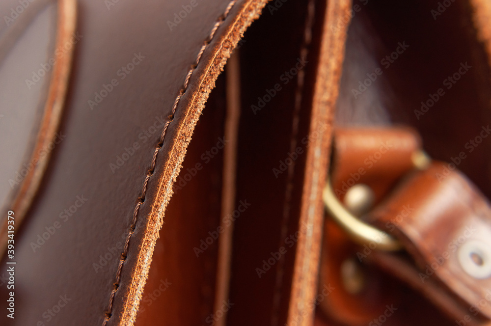 Fototapeta Fashionable brown women's bag made of genuine leather close-up. Leather bag texture. Fashion concept Details of leather bag belt metal buckle clasp thread stitching macro shot Stylish female accessory