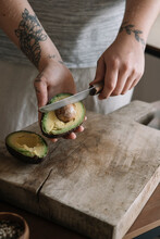 Woman Cutting Avocado While St...