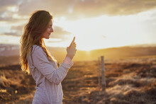 Iceland, Young Woman Using Smartphone At Sunset