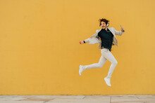 Businessman Jumping In The Air In Front Of Yellow Wall Listening Music With Headphones And Smartphone