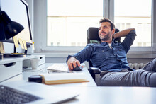 Relaxed Man Sitting At Desk In Office Looking At Computer Screen