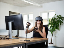 Happy Woman Wearing VR Glasses At Desk In Office