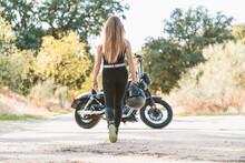 Blond Woman Holding Helmet While Walking Towards Motorcycle On Road