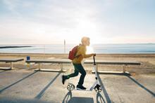 Boy Riding Scooter On Beach Pr...