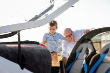 Grandson And Grandfather Inside Airplane At Airfield