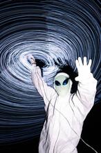 Man In White Alien Costume Standing Under Light Trails At Night