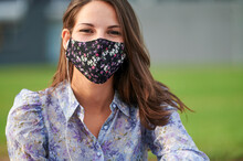 Woman Wearing Protective Face Mask While Sitting In City
