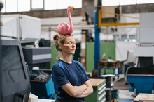 Young Woman Working As A Skilled Worker In A High Tech Company, Balancing A Pink Flamingo On Her Head
