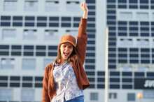 Young Woman Giving Winning Expression While Standing On Street In City