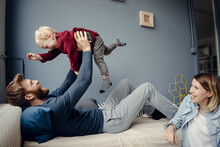 Happy Family Playing With Their Son At Home