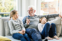 Grandfather Talking To Two Girls On Sofa In Living Room
