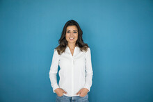 Portrait Of Smiling Woman Standing In Front Of Blue Wall