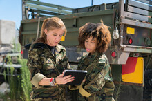 Female Military Soldiers Discussing Over Digital Tablet Against Truck On Sunny Day