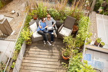 Young Couple Relaxing On Their Balcony, Sitting On Couch, Using Laptop