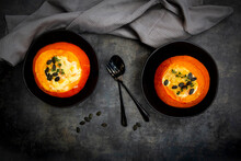 Studio Shot Of Two Hokkaido Pumpkins Stuffed WithÔøΩcamembertÔøΩcheese, Thyme And Pumpkin Seeds