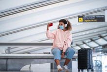 Young Woman Taking Selfie While Listening Music Through Headphone At Airport