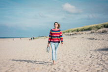 Mature Woman Walking Barefoot On The Beach
