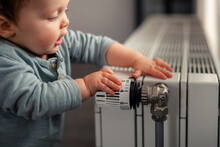 Baby Boy Playing With Thermostat Of Heater