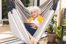 Mature Woman Using Digital Tablet While Sitting On Hammock At Home
