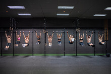Male And Female Athletes Hanging On Rod At Gym