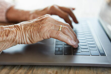 Hand Of Senior Woman Typing On...