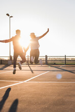 Carefree Young Couple Jumping On Parking Levelat Sunset