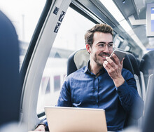 Smiling Businessman In Train Using Cell Phone