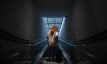 Young Woman Holding Suitcase Standing On Escalator At Airport