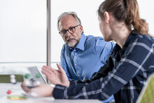 Mature Businessman And Young Woman With Atomic Model Talking In Conference Room