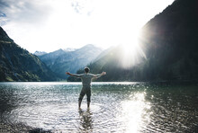 Austria, Tyrol, Hiker Standing With Outstretched Arms In Mountain Lake