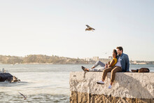 Young Couple Sitting On Pier At The Waterfront Enjoying The View, Lisbon, Portugal