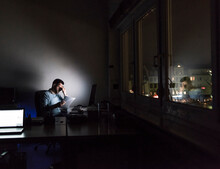 Exhausted Businessman Sitting At Desk In His Office By Night