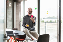 Smiling Young Businessman Sitting At The Window Juggling With Balls