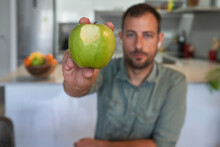 Man Showing Bitten Apple While Sitting At Home