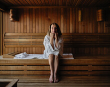 Senior Woman With Hand On Chin Sitting On Wooden Sauna