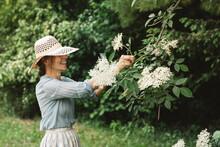 Smiling Woman Picking Flower F...