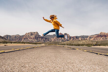 Carefree Woman Jumping On Country Road Against Sky, Nevada, USA