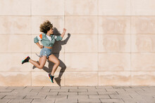 Young Woman Jumping Against Wall During Sunny Day