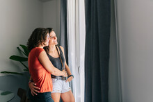 Female Friends Looking Through Window While Standing At Home