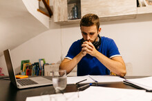 Dedicated Young Male Student Sitting With Hands Clasped While Doing Homework At Table