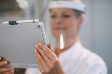 Close-up Of Female Scientist Wearing Protective Face Shield While Using Digital Tablet At Laboratory