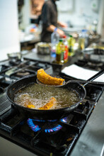 Cooking Pan On Gas Stove Burner With Chef Working In Background At Kitchen