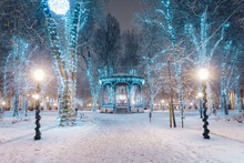 Snow Covered Footpath Amidst Illuminated Trees During Advent At Night