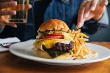 Hand Grabbing Cheeseburger Wit...