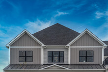 Upscale American House Façade With Vertical Beige Vinyl Siding White Accents, Black Framed Aluminum Windows Metal Roof Cover Over The Porch, Double Gable Roof With Dreamy Blue Sky In The USA