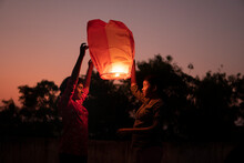 Sisters Holding And Releasing Chinese Lantern At Outdoors In The Evening Time