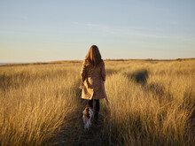 Young Women With Dog Walk At The Field With High And Dry Grass