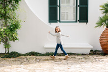 Young Girl Walking In Front Of A White Wall