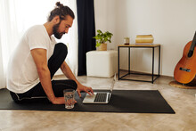 Man Sitting On An Mat At Home Using A Laptop